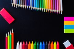 School and drawing supplies, on black background. Colored pencils, pencils, sticky note, eraser, sharpener and crayons. stock image
