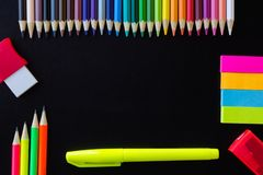 School and drawing supplies, on black background. Colored pencils, pencils, sticky note, eraser, sharpener and highlighter. With copy space royalty free stock image