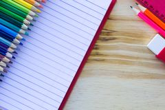 School and drawing supplies, on wooden table. Exercises book, colored pencils, eraser, pencil and ruler. stock photos