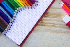 School and drawing supplies, on wooden table. Exercises book, colored pencils, eraser and ruler. With copy space. royalty free stock photo