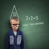 School dunce. School boy wearing a dunce cap against a blackboard with incorrect sums and must try harder note Stock Image