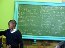 School Duties. An african child in a school uniform carries out his weekly school duties and writes down his spelling words in Cape Town, South Africa royalty free stock photo