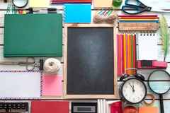 School education background objects. Aerial view of stationery objects with blackboard in the centre Stock Photography