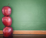 School Education ChalkBoard with Apples. Three red apples are stacked up and leaning against a green school chalkboard. Use the photo for a classroom, school or Royalty Free Stock Photo