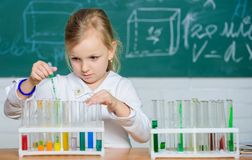 School education. Interesting approach to learn. Kid like to experiment. Explore and investigate. School lesson. Girl. Cute pupil play with test tubes and stock images