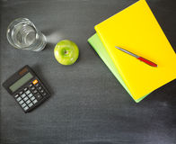 School and Education Objects. Top view of a blackboard with school supplies - an apple, textbooks and a calculator Stock Image