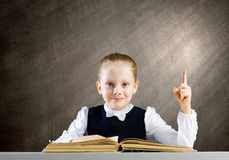 School education. Schoolgirl at lesson with opened book against sketch background stock photos