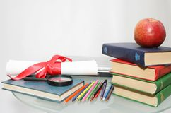 School and education theme. Diploma and red apple on a pile of books Stock Photo