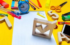 School elections concept. Election check box and school accessories on a desk on a yellow background. education. stationery, watch. Es, colored pens, phone royalty free stock image