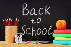 School en bureaulevering op een zwarte bordachtergrond Terug naar School stock fotografie