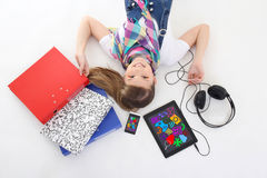 School and entertainment concept - teenage girl lying with table Royalty Free Stock Images