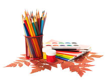 School equipment with pencils, paints , brushes and  autumn leaves. Stock Photography