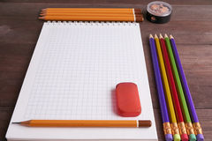 School exercise book with colorful pencils. School exercise book with lot of colorful pencils, eraser and sharpener. low angle shot Royalty Free Stock Images