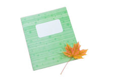 School exercise book and yellowed maple leaf on light background Royalty Free Stock Photography