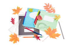 School exercise books, school supplies and yellow and red leaves Royalty Free Stock Photography