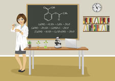 School female teacher giving lecture in chemistry class next to blackboard Royalty Free Stock Images