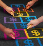 School Financing. And education business concept as a group of children drawing a hopscotch game on a floor with dollar signs as a symbol of student loans and Royalty Free Stock Photography