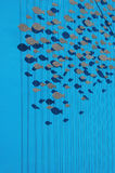 School of fish. The welcome logo of genova's acquarius representing a group of fishes on a blue background Royalty Free Stock Images