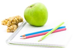 School and food. Spiral notebook, colorful pencils, apple and cereals for afternoon Royalty Free Stock Photography