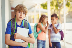 School friends bullying a sad boy in corridor Royalty Free Stock Photo