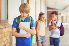 School friends bullying a sad boy in corridor Stock Photos