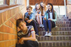 School friends bullying a sad boy in school corridor. At school royalty free stock images