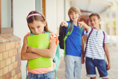 School friends bullying a sad girl in corridor Royalty Free Stock Photos