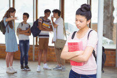 School friends bullying a sad girl in corridor. At school Stock Images