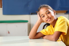School girl 10 relaxed while sitting at her classr. Young school girl, 10, wearing yellow t-shirt sitting to her desk in thoughtful relaxed pose - Canon 5D MKII stock image