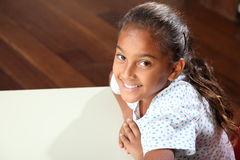 School girl 10 relaxed while sitting at her classr. Young school girl, 10, wearing yellow t-shirt sitting to her desk in thoughtful relaxed pose - Canon 5D MKII stock photos