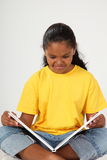 School girl 9 sitting enjoying reading a book Royalty Free Stock Image