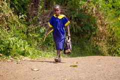 School girl in Africa. A girl on her way home from school along a road near Bomet, Kenya Stock Photography