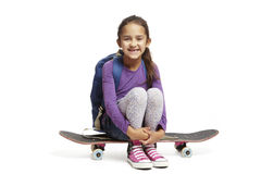 School girl with backpack sitting on a skateboard Royalty Free Stock Photos