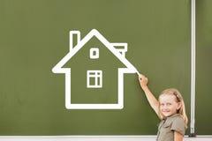 School girl at blackboard. Cute little girl drawing house on blackboard Stock Photos