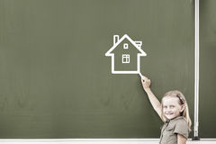 School girl at blackboard. Cute little girl drawing house on blackboard Royalty Free Stock Photography