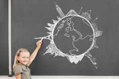 School girl at blackboard. Cute little girl drawing travel concept on blackboard Stock Images