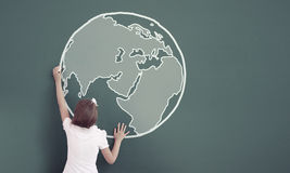 School girl at blackboard. Cute little girl standing with back and drawing planet on blackboard Stock Photos