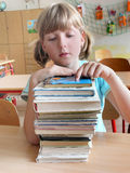 School girl with books. Blond school girl in classroom with a pile of books in front of herself stock image