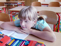 School girl in classroom. Blond school girl sitting at her desk in classroom listening lesson royalty free stock photo