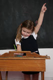 School girl at desk. A young school girl or student at an old desk near a blackboard Stock Photo