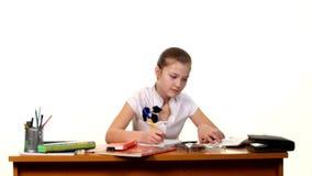 School girl doing her homework and writes essay on stock video