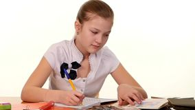 School girl doing her homework and writes essay on stock video footage