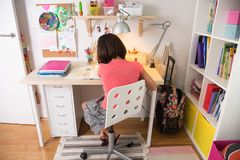 Young girl doing homework. School girl doing homework at home in her desk. Back view Royalty Free Stock Images