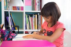 Young girl doing homework. School girl doing homework at home in her desk Royalty Free Stock Photos