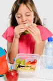 School girl eating her packed lunch sandwich. Young elementary school girl eating enjoying her healthy sandwich from her lunch box filled with nutritious food royalty free stock photo