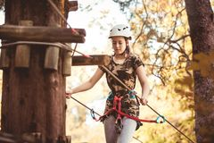 School girl enjoying activity in a climbing adventure park. Happy school girl enjoying activity in a climbing adventure park on a summer day royalty free stock images