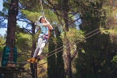 School girl enjoying activity in a climbing adventure park Stock Image