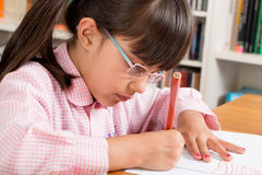 School girl with eye glasses. Doing homwork stock images