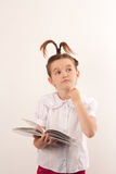 School girl with funny hair style reading a book Royalty Free Stock Photography