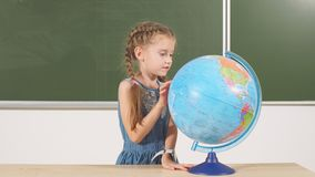 School girl with globe in classroom chalkboard on background stock video footage